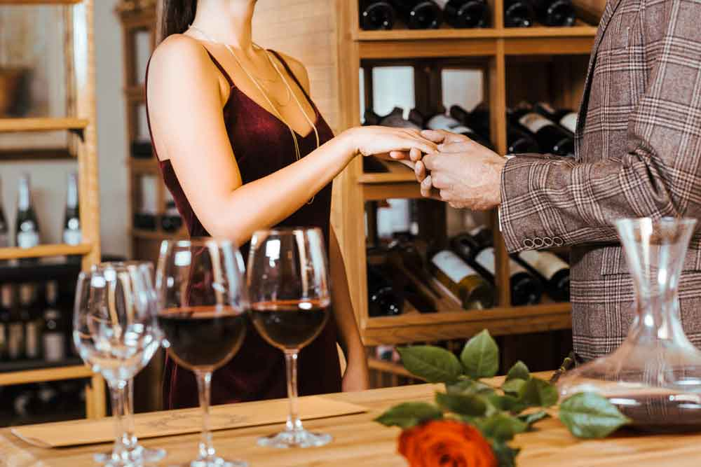 man holding the hand of a woman with wine glasses in the foreground