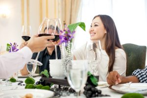 people sitting at a restaurant table all making a toast with glasses of wine